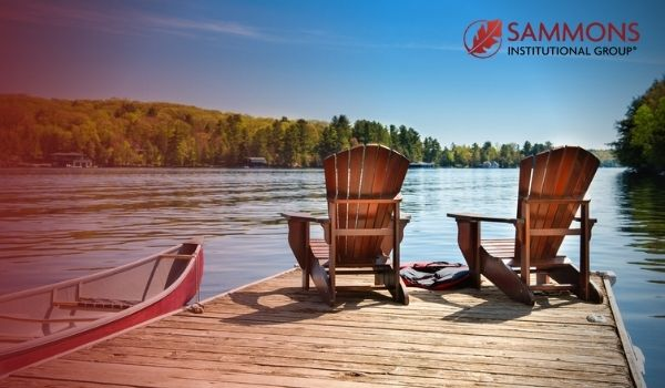Two chairs sit on a deck looking out on a lake